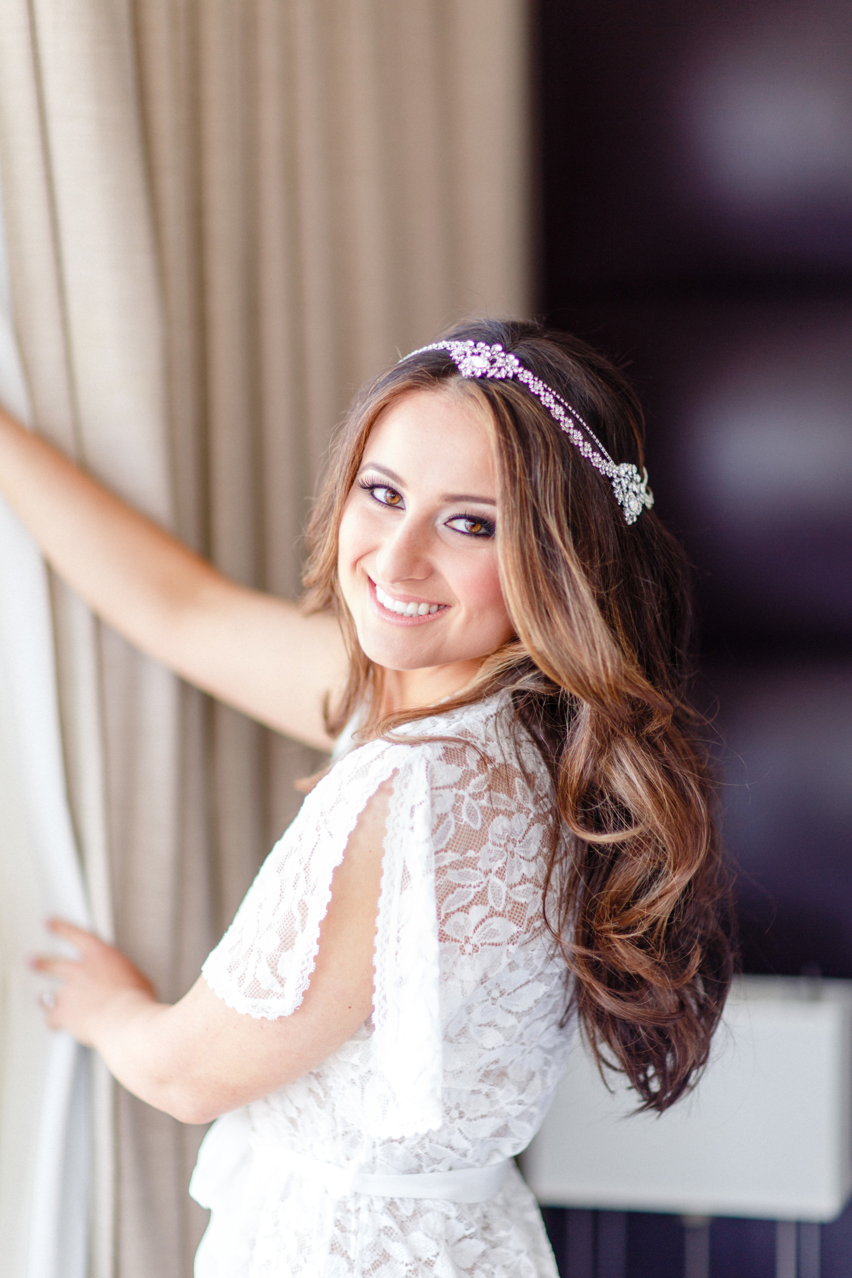 Bride with dark eyeliner and long hair in a headband reaches for her gown