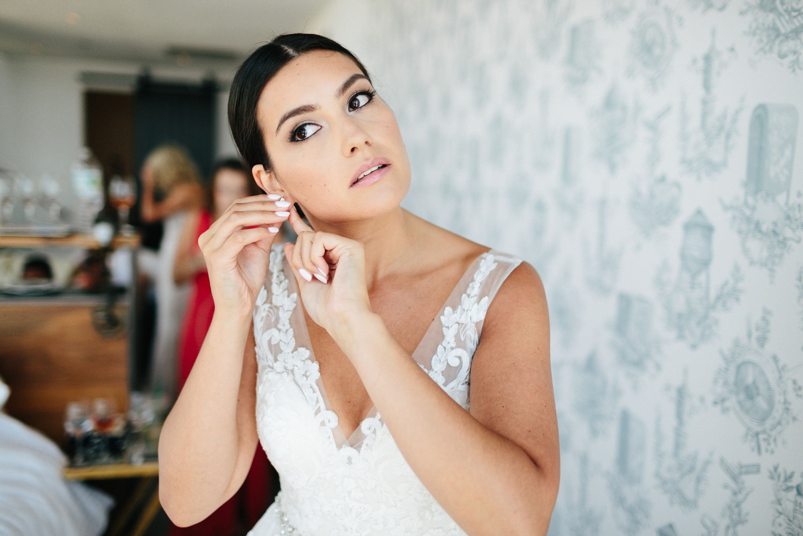 Bride with movie star face puts on her earrings before ceremony at Wythe Hotel in Williamsburg, Brooklyn