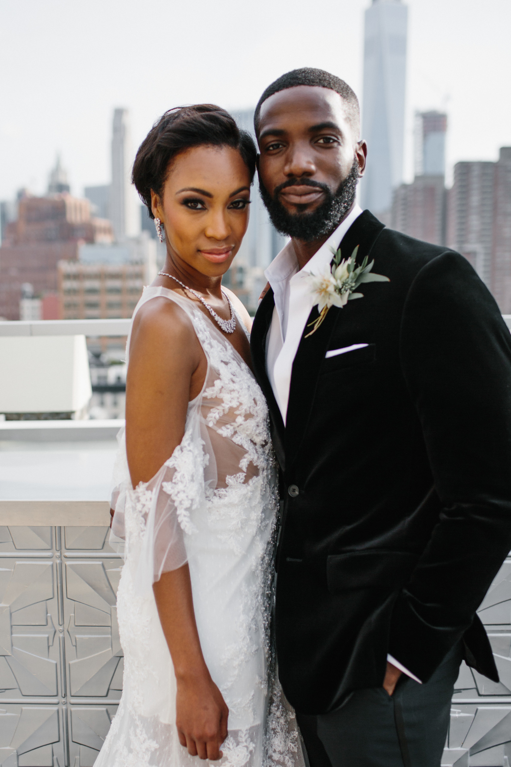 Chic bride in white dress with open shoulders, defined eyes and brows, glowing skin, poses with her groom at Tribeca Rooftop in New York City
