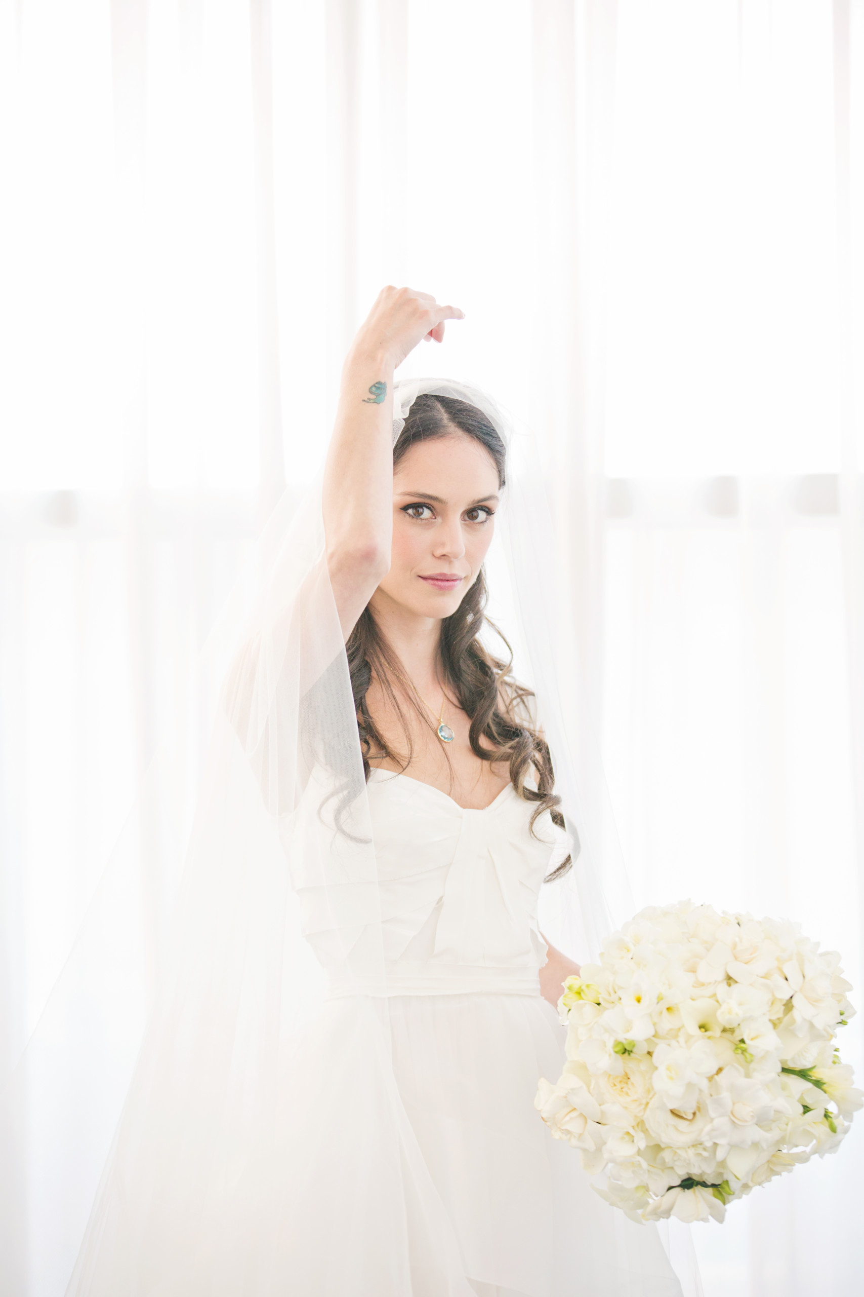 Bride with long dark hair and big smokey eye makeup lifts her veil and shows off her wrist tattoo, photographed at Chelsea Piers Pier 60