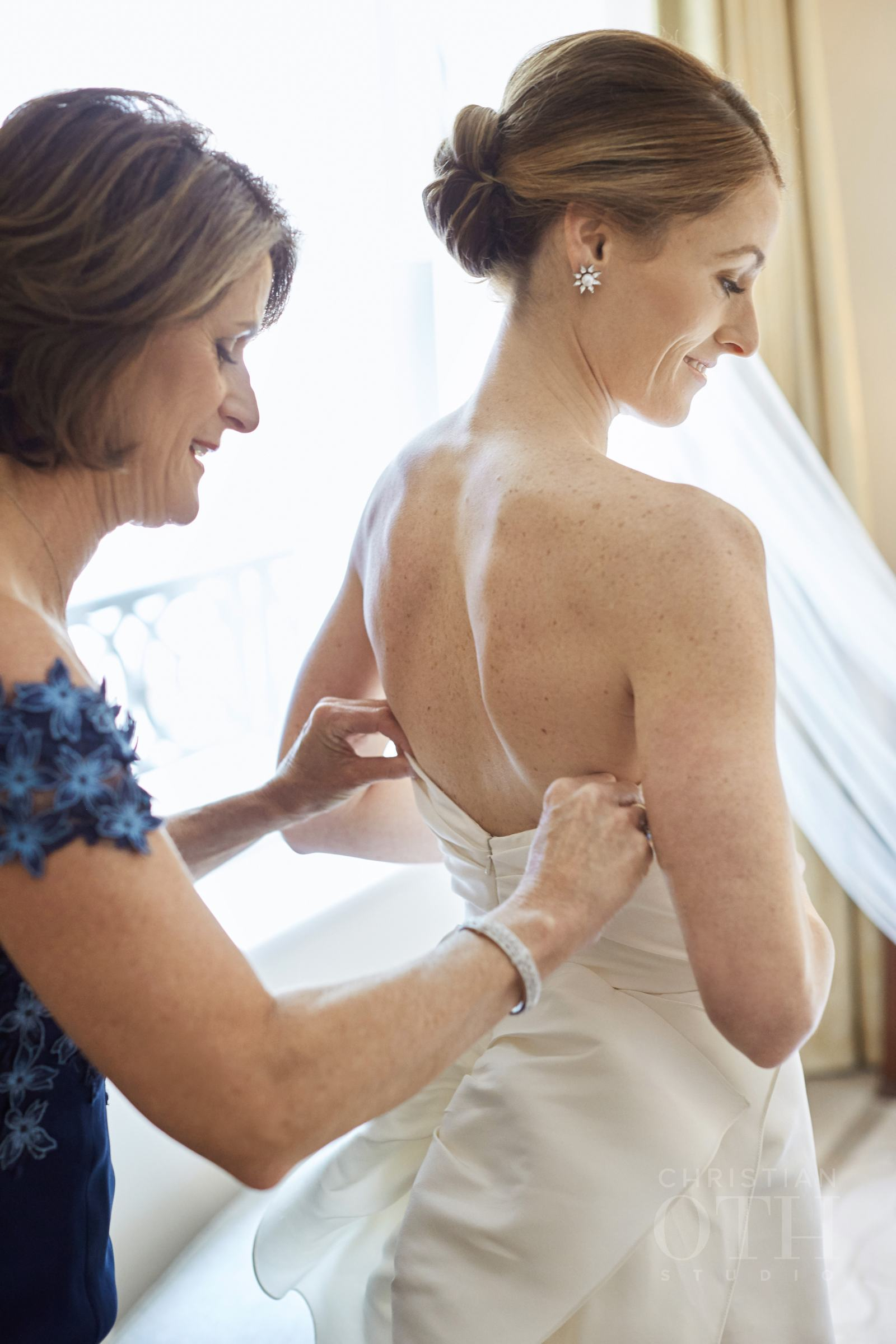 Mother of the bride adjusts dress on bride with modern, chic chignon, before wedding at Peninsula Hotel in New York City
