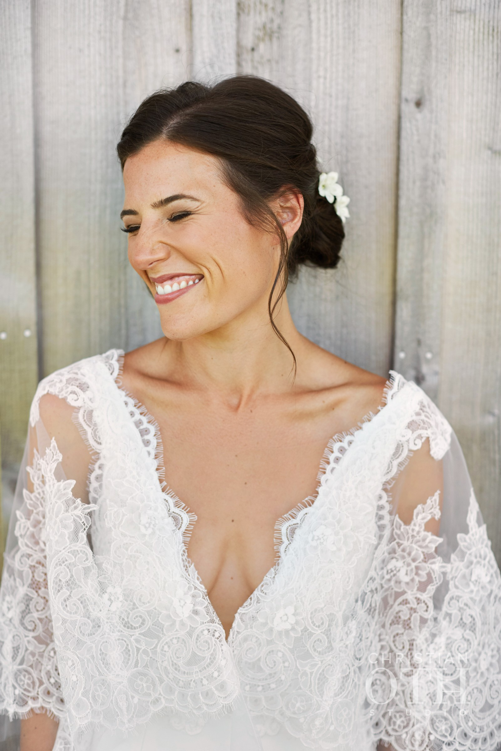 Excited bride with bronzy skin and rose lipstick smiles before her wedding at Crow's Nest in Montauk