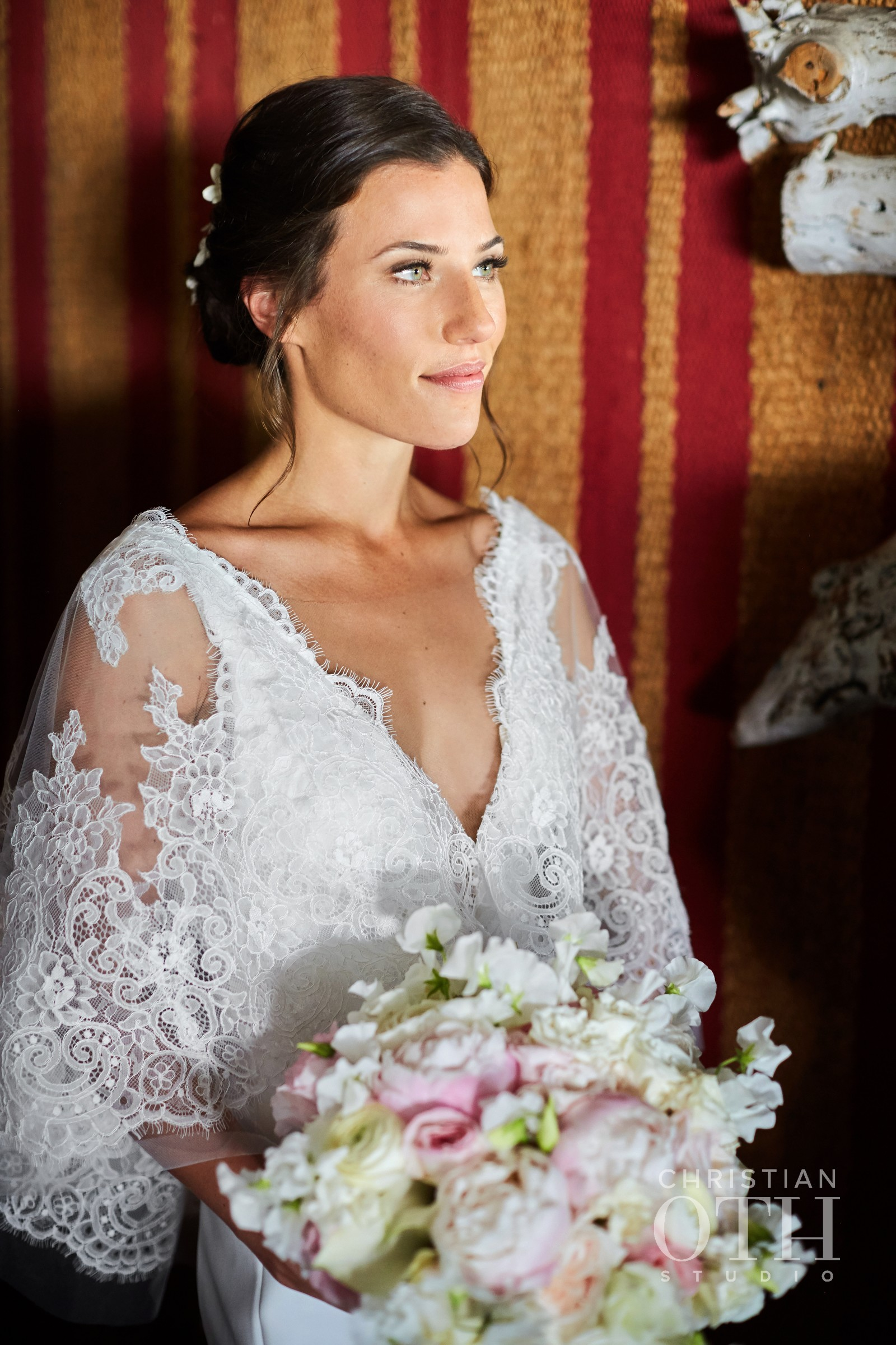 model bride with tan skin and defined eyes poses at Crow's Nest in Montauk before her wedding ceremony
