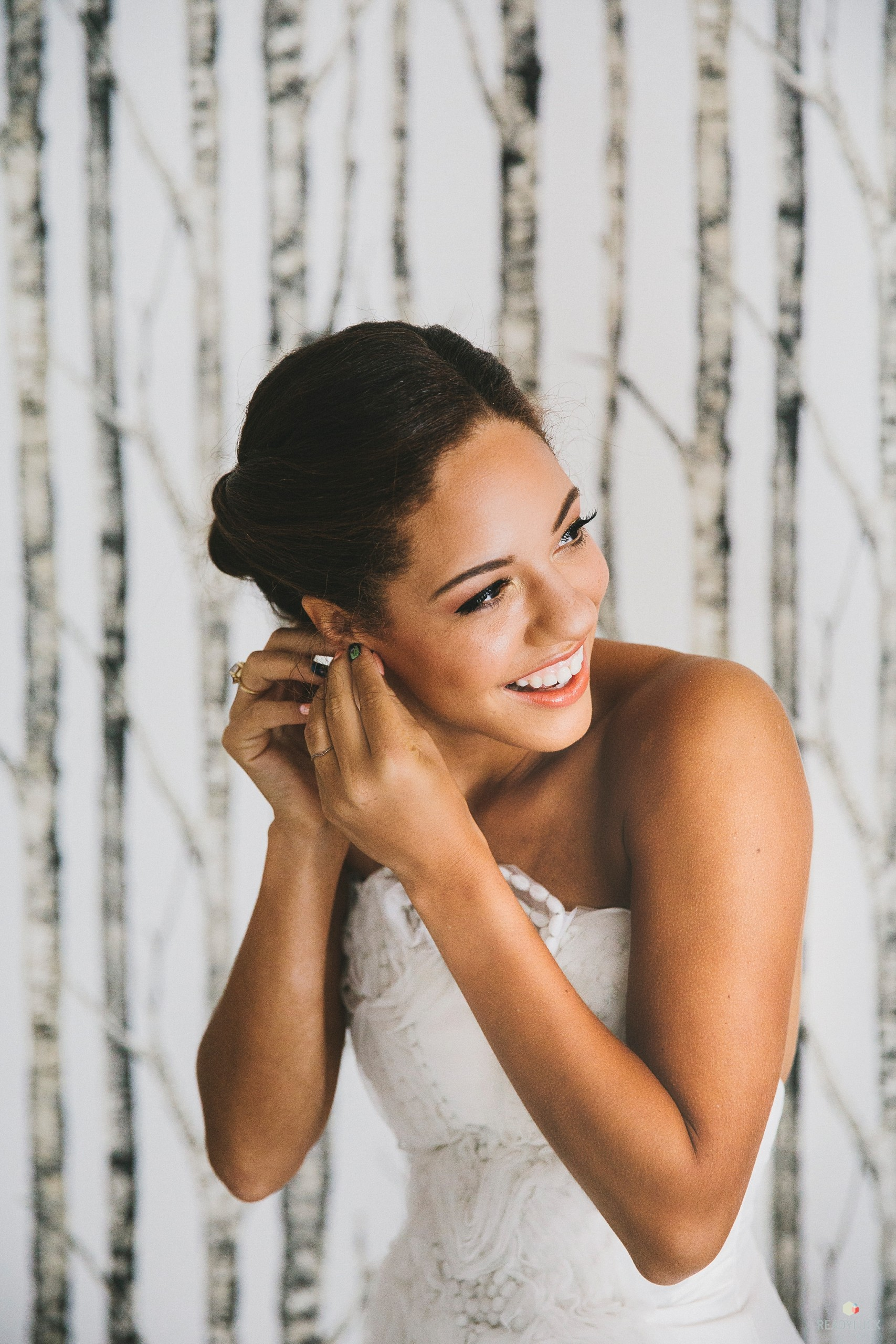 Bride with defined eyes and lashes, peach lips, and perfect skin adjusts her earrings before her ceremony at Cedar Lakes Estate