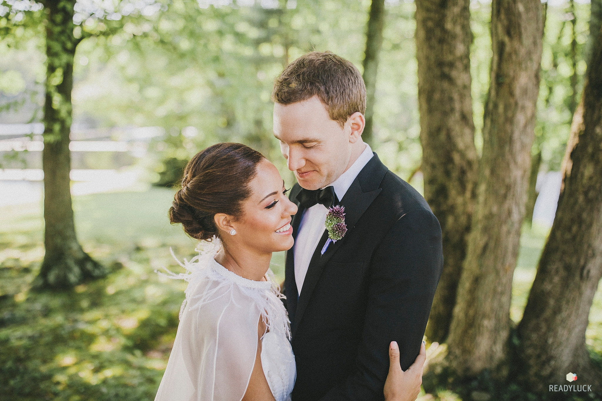 Bride with defined eyes, lashes, peach lips, and perfect skin embraces her husband while wearing a feather cape from Carol Hannah at Cedar Lakes Estate
