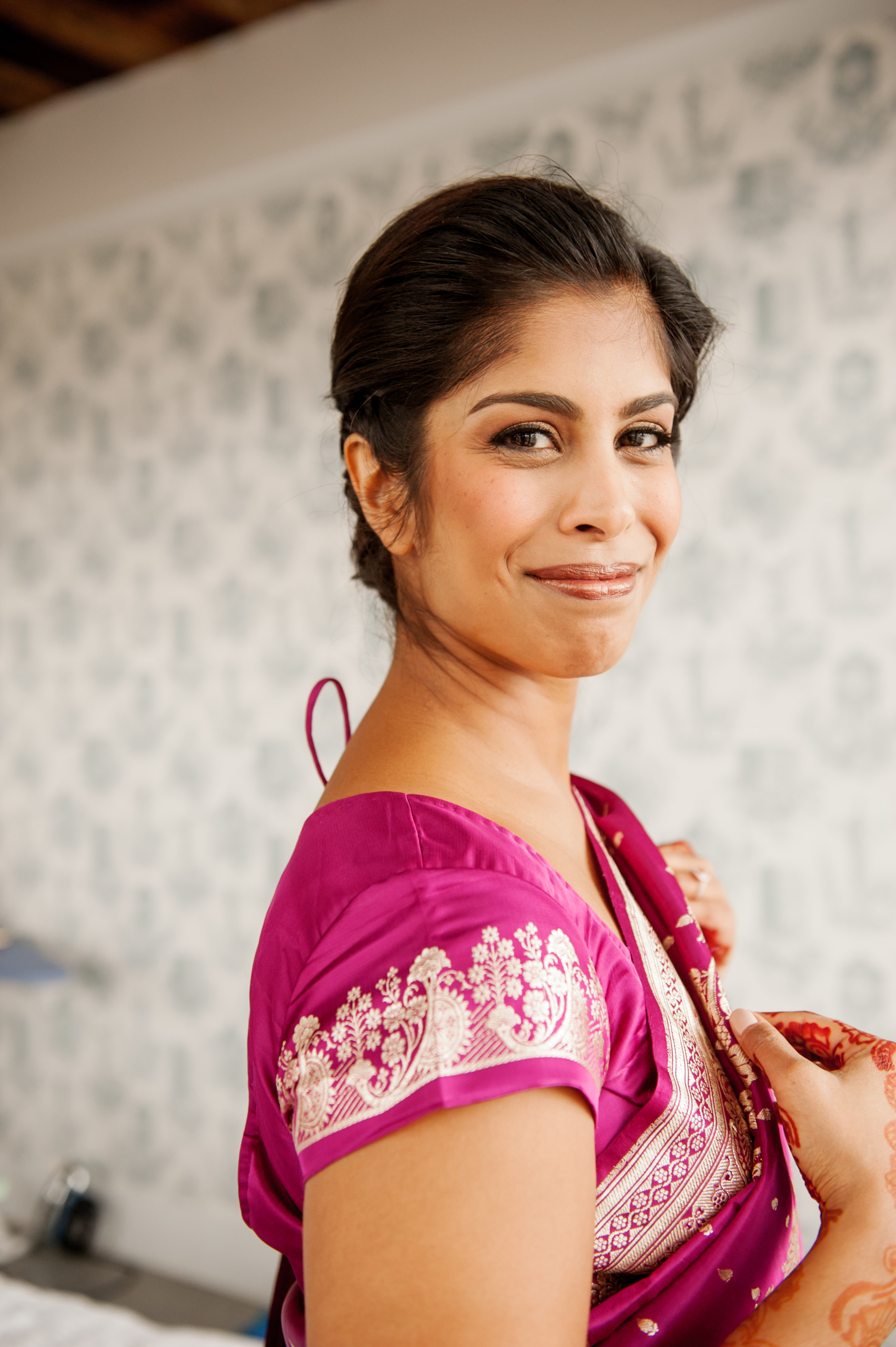 Indian bride with soft makeup and defined eyes, wearing magenta sari, smiles at the Wythe Hotel in Williamsburg, Brooklyn