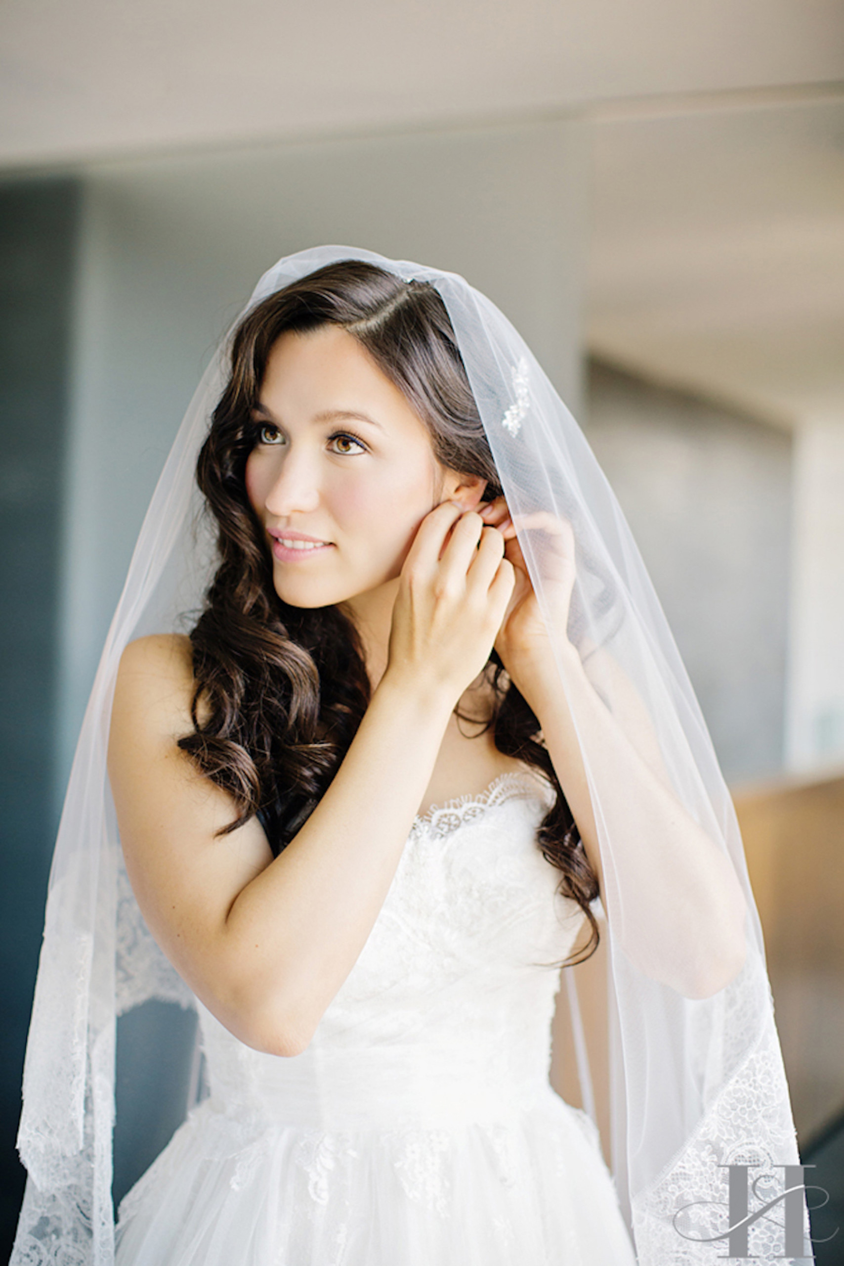 Beautiful brunette bride with very soft chic makeup and long Hollywood waves with lace veil in SoHo, New York City