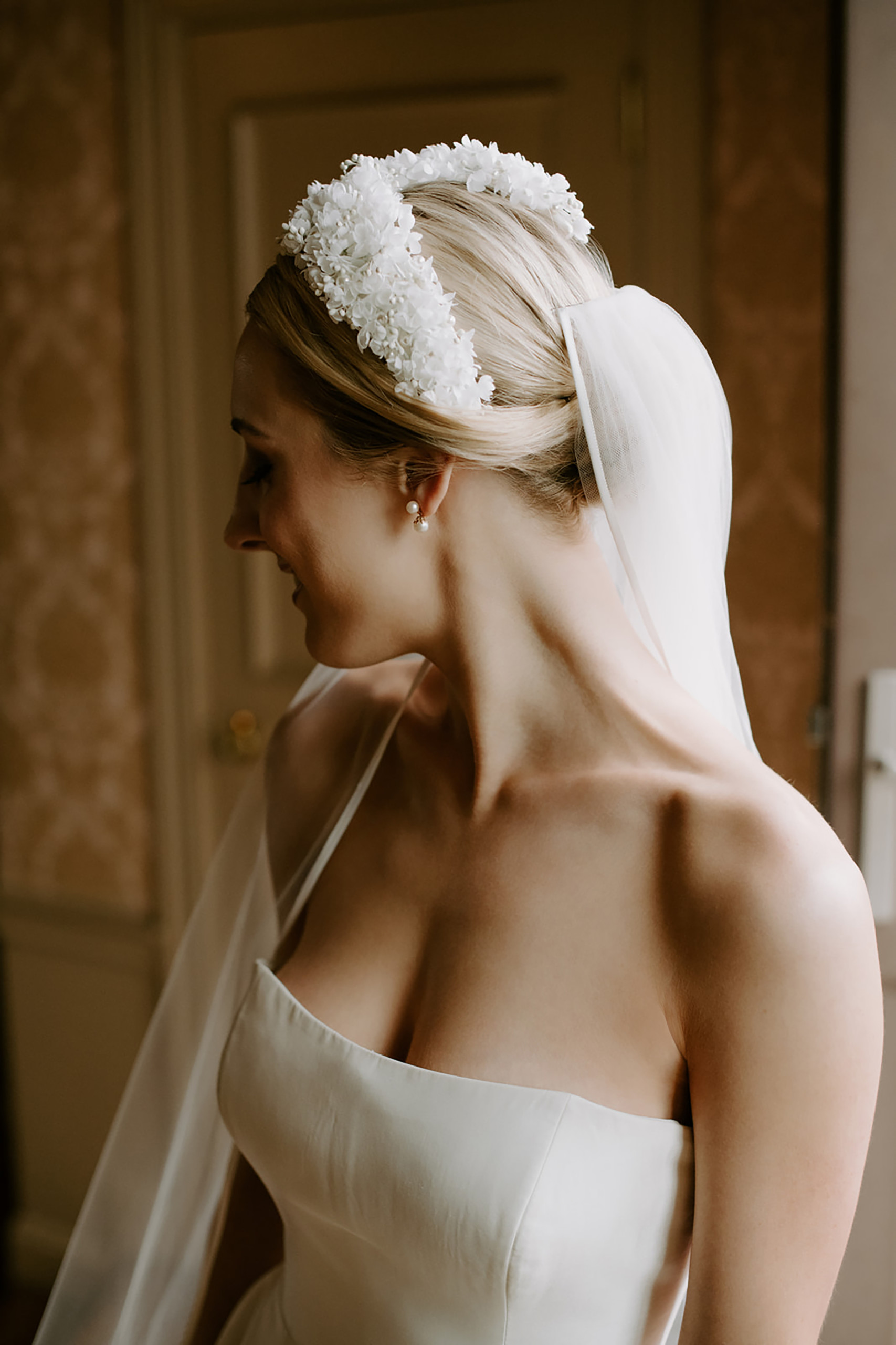 Blonde bride with classic strapless dress and elaborate flowered headband over her simple chignon, photographed at Oheka Castle