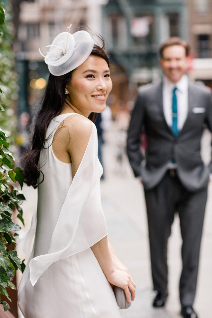 Bride in chic day white day dress with little white hat poses on New York City street