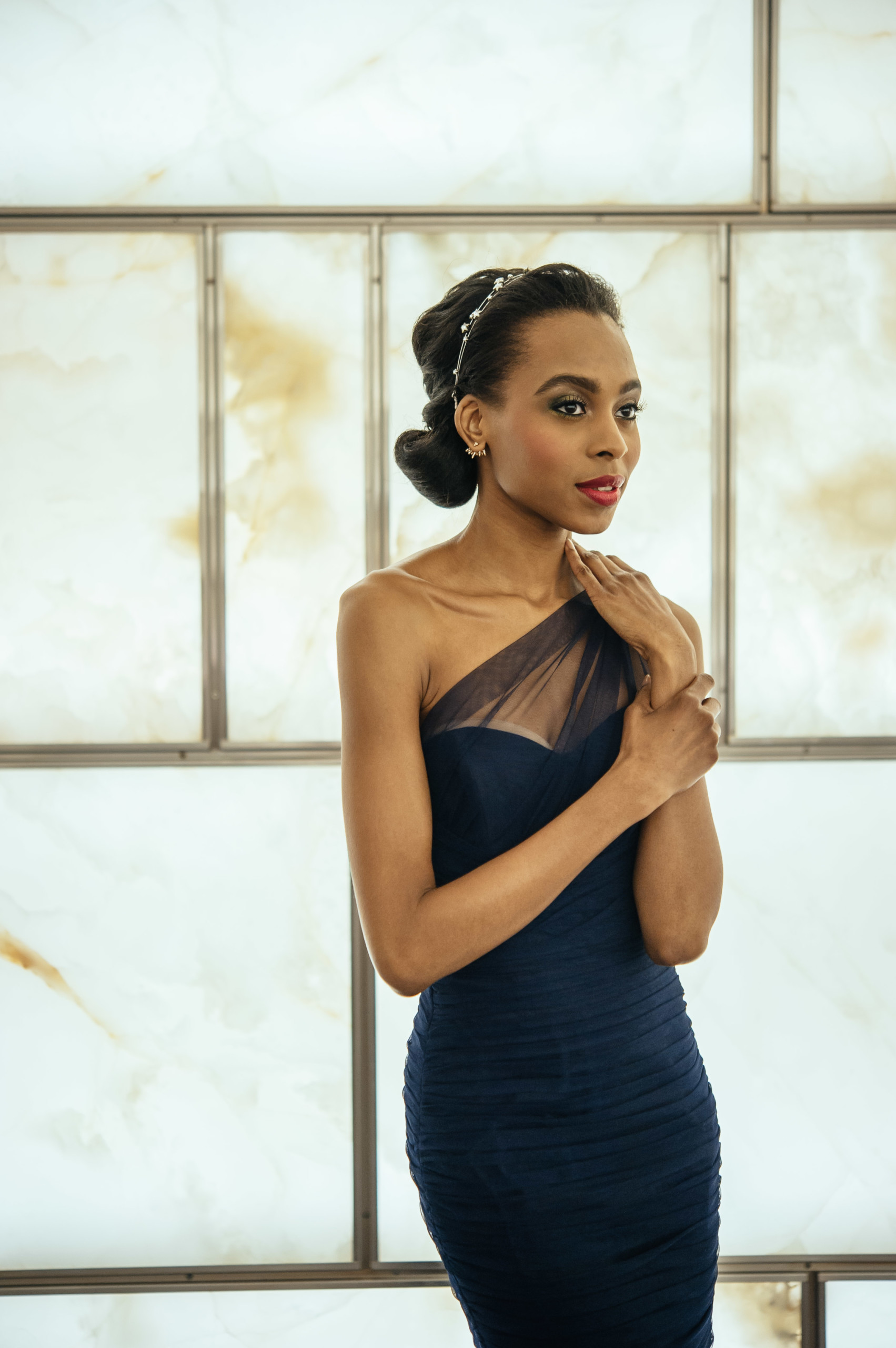 Chic bridesmaid in one-shoulder navy gown with updo and sparkly headband, and dramatic makeup
