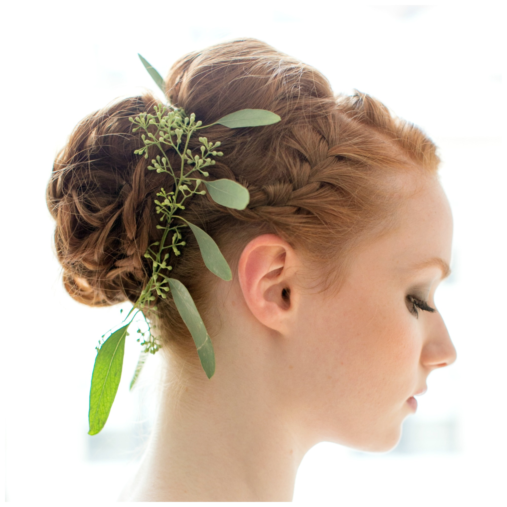 Bride with red hair knotted into braided bun, decorated with leaves
