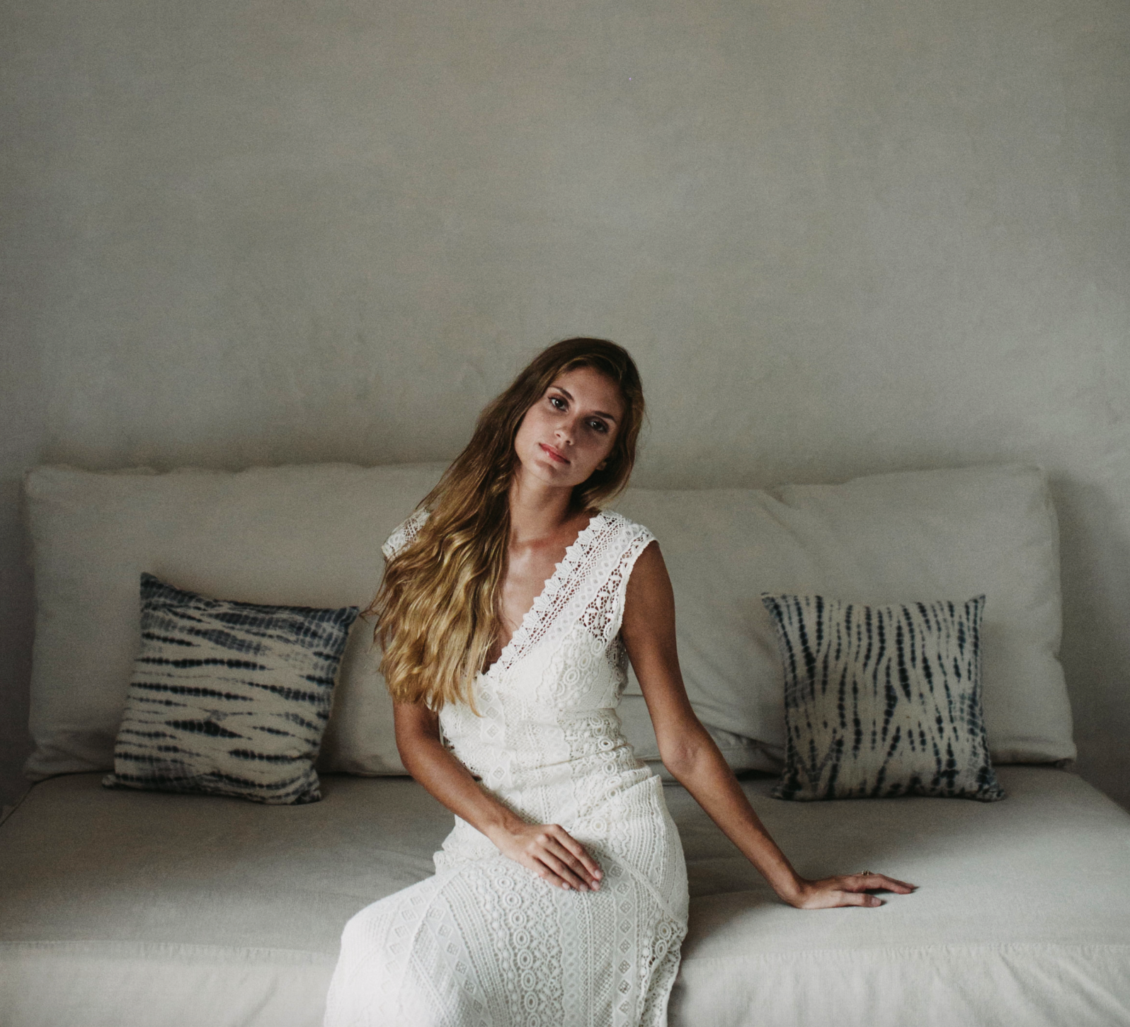 Bride with very long hair relaxing in Rebecca Schoneveld dress at resort in Tulum, Mexico, shot by Chellise Michael