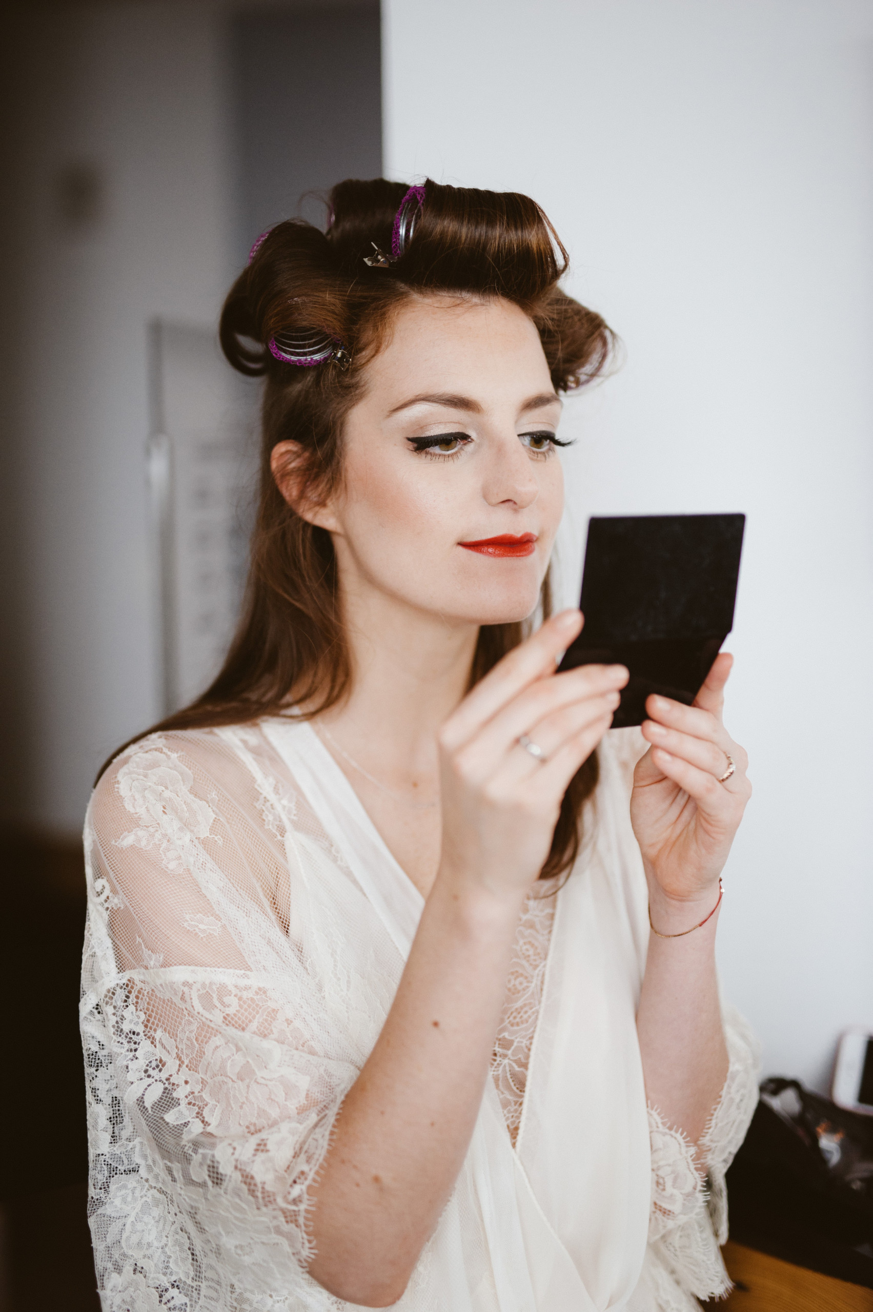 Bride with long lashes, cat eye, and red lips looks at herself in the mirror at the Wythe Hotel in Williamsburg, Brooklyn