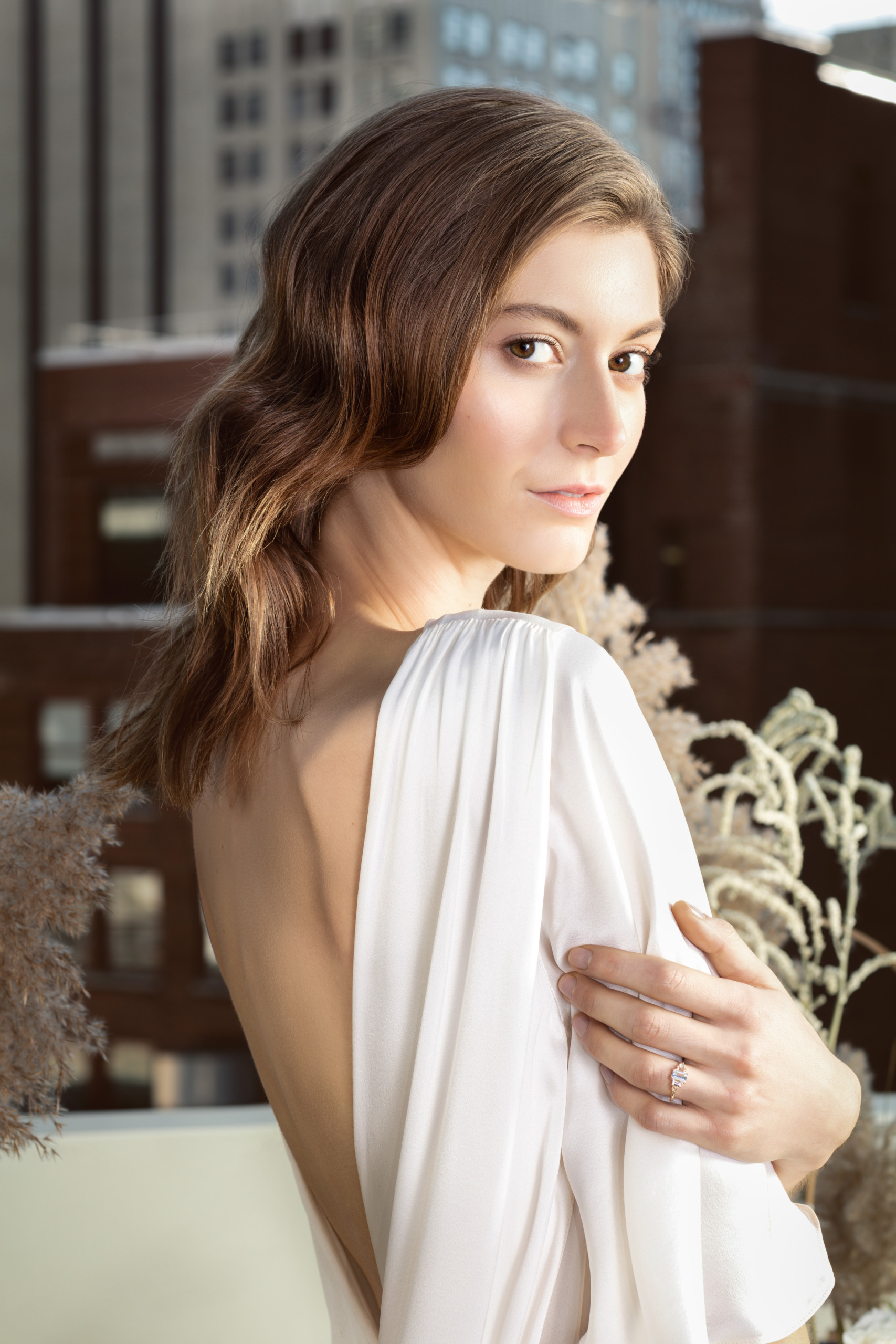 Bride with dramatic backless dress and very soft makeup and hair poses on Sofitel rooftop in New York City