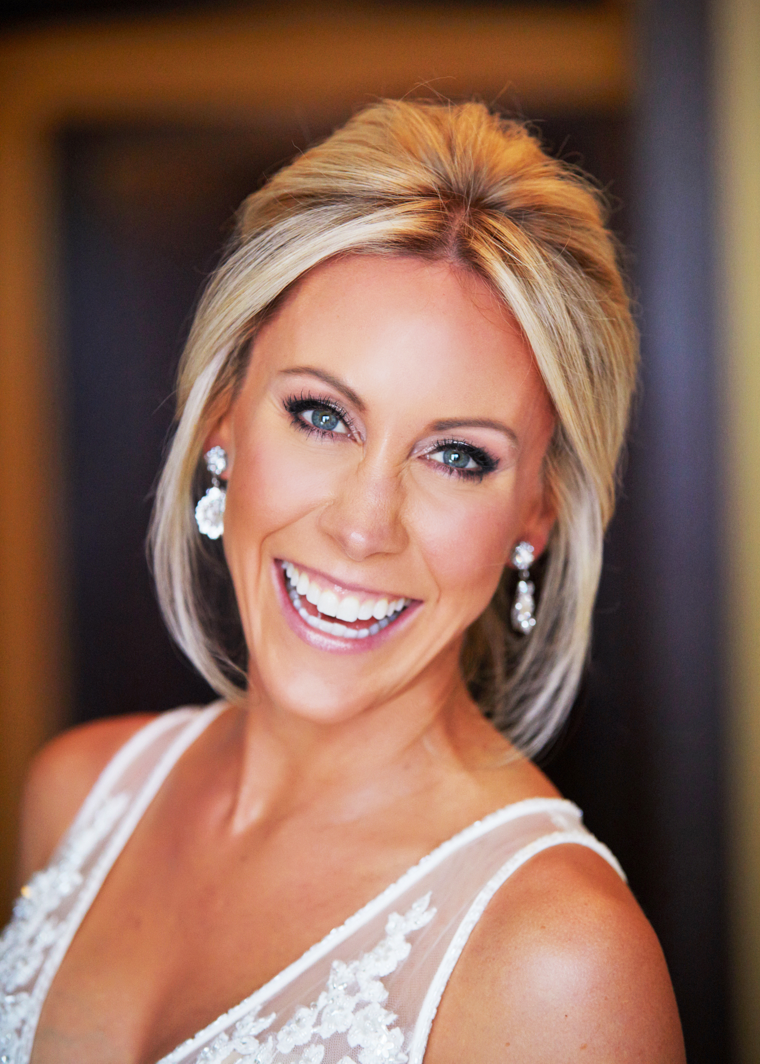 Blonde bride with defined eyes and lashes, and contoured cheeks smiles before her wedding at the Four Seasons in Vail, CO