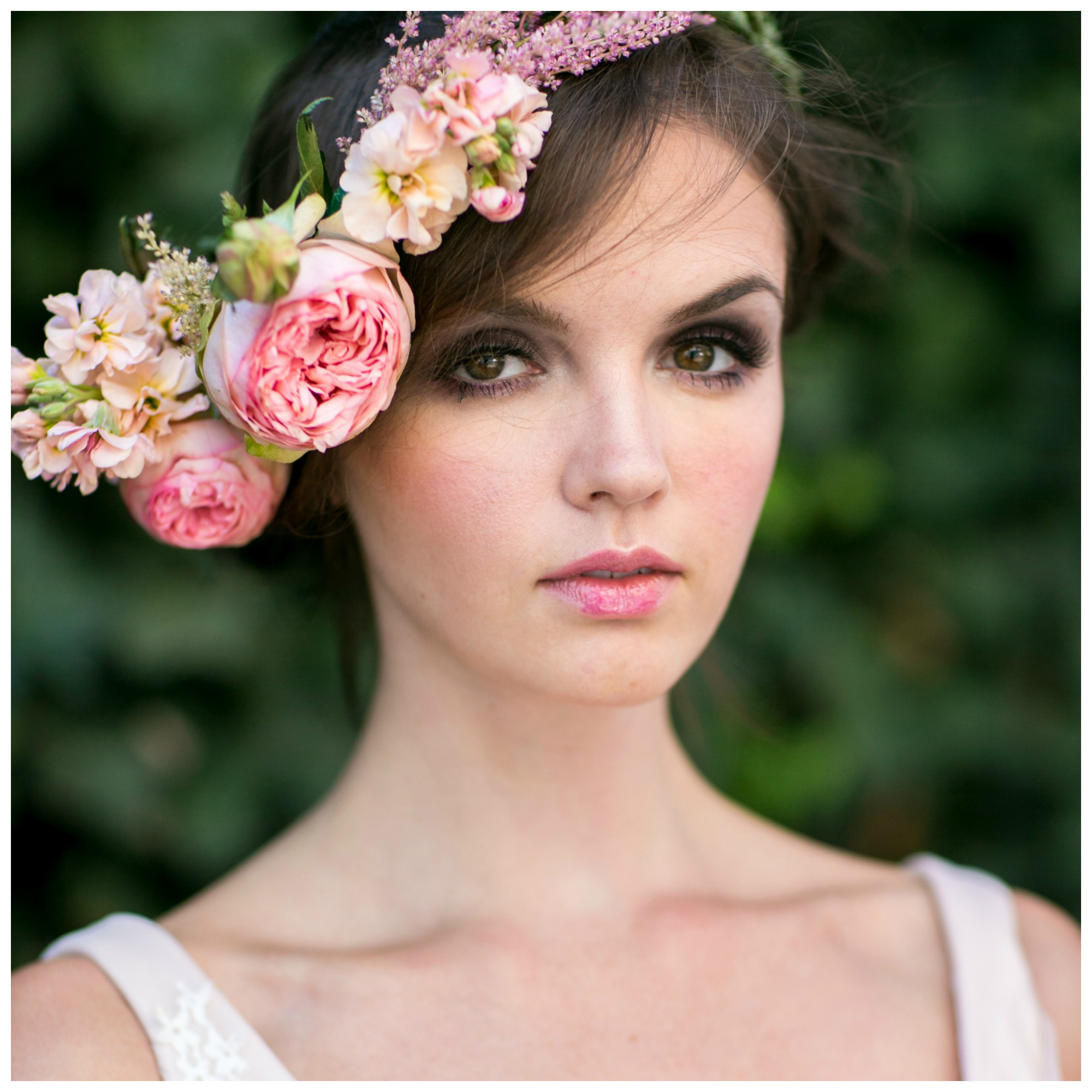 Model in wedding gown with smokey grey eye shadow, pink lips, and fresh flower crown, posing in SoHo New York City