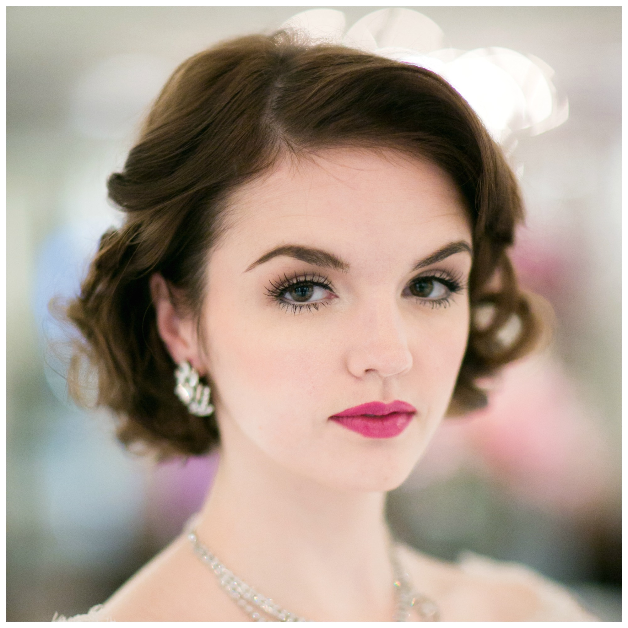 Bride in classic hair, earrings, with strong brows and perfect pink lipstick