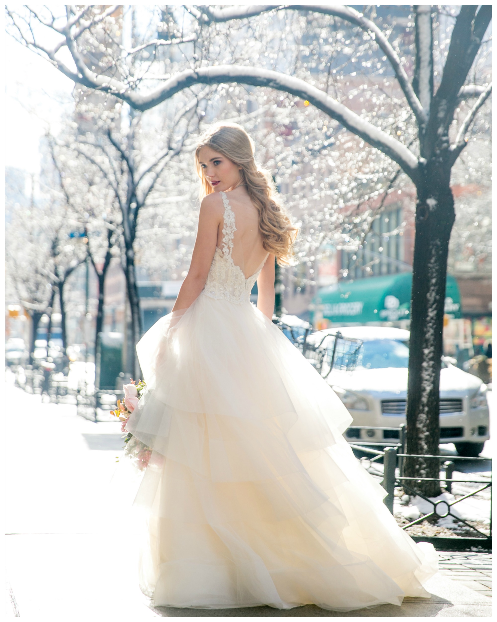 Bride in full ball gown with open back, long blond hair curled, posing on a snowy street in New York City