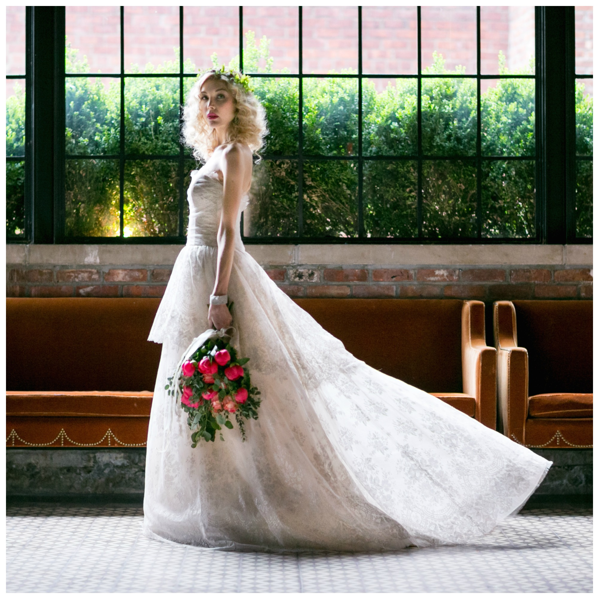 Bride with blonde curly hair and bright pink lip poses in the Bowery Hotel, New York City