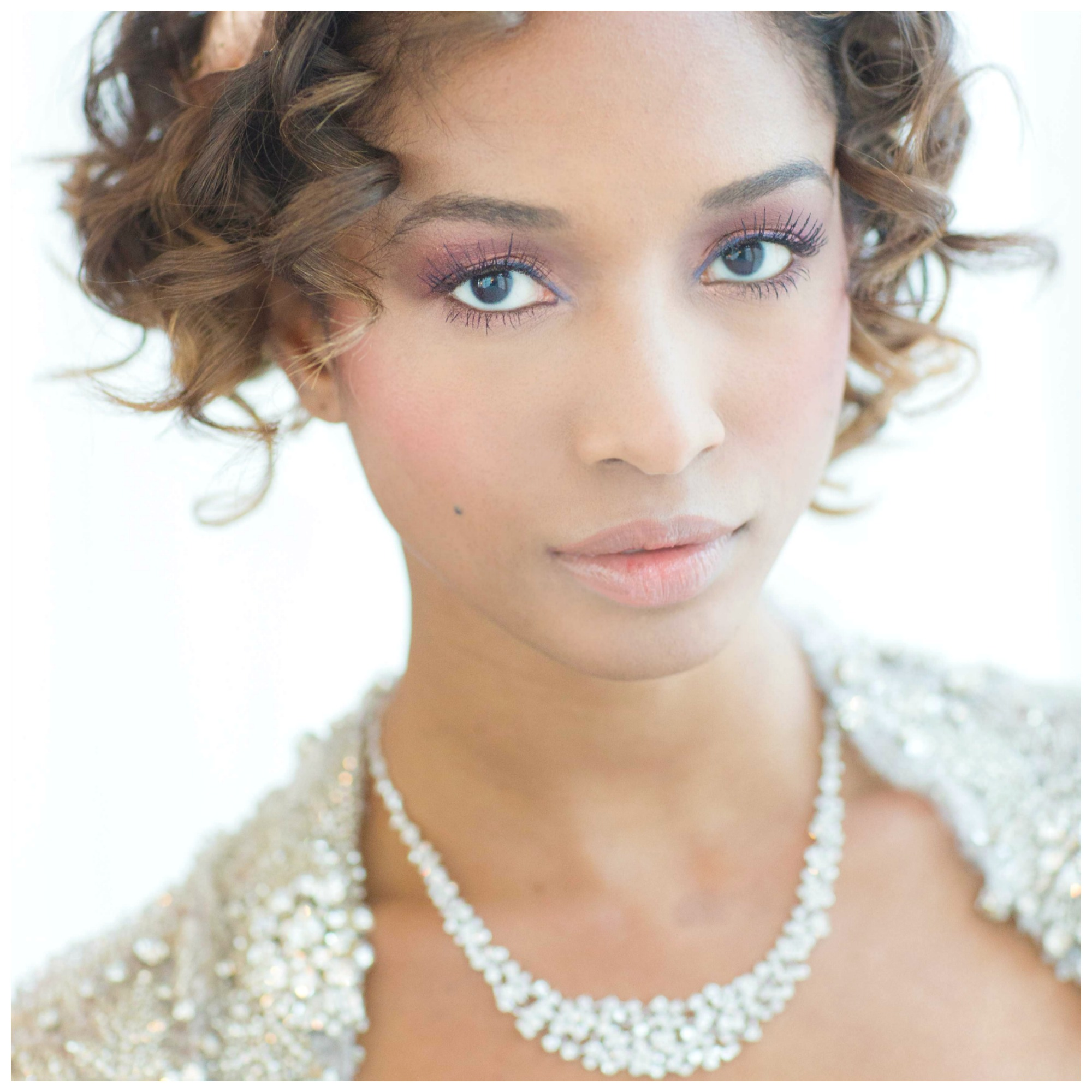 Bride in sparkling wedding gown, diamond necklace, and soft romantic makeup